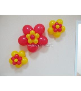 Цветочки красно-желтые из шариков на стене.